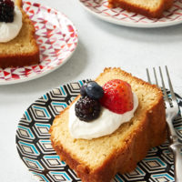 slice of Sour Cream Pound Cake topped with sweetened whipped cream and fresh berries
