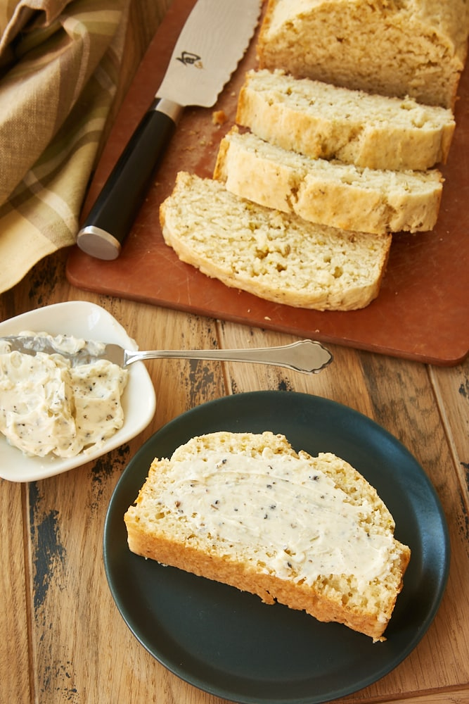 slice of Easy Herbed Quick Bread spread with garlic compound butter