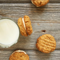 Peanut Butter Sandwich Cookies on a pale wooden surface