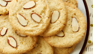 overhead view of Almond Cookies on a white and brown speckled plate