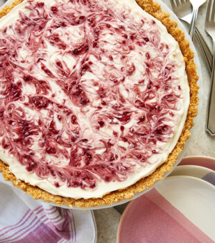 No-Bake Raspberry Cheesecake on a milk glass stand