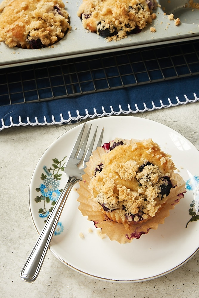Blueberry Coffee Cake Muffin on a blue floral-edged plate with a partial view of more muffins in a muffin pan in the background