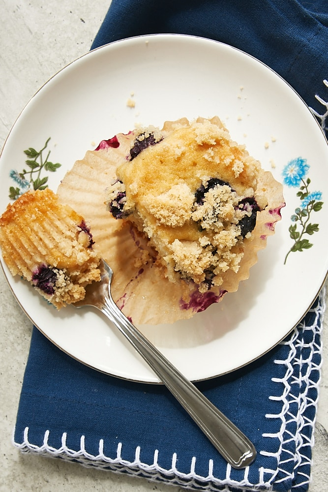 overhead view of a Blueberry Coffee Cake Muffin on a white plate with a blue floral edge