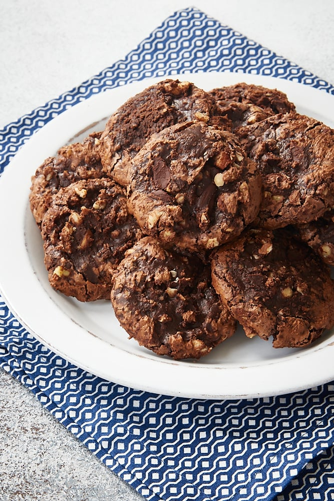 Flourless Chocolate Hazelnut Cookies piled on a white plate on a blue and white napkin