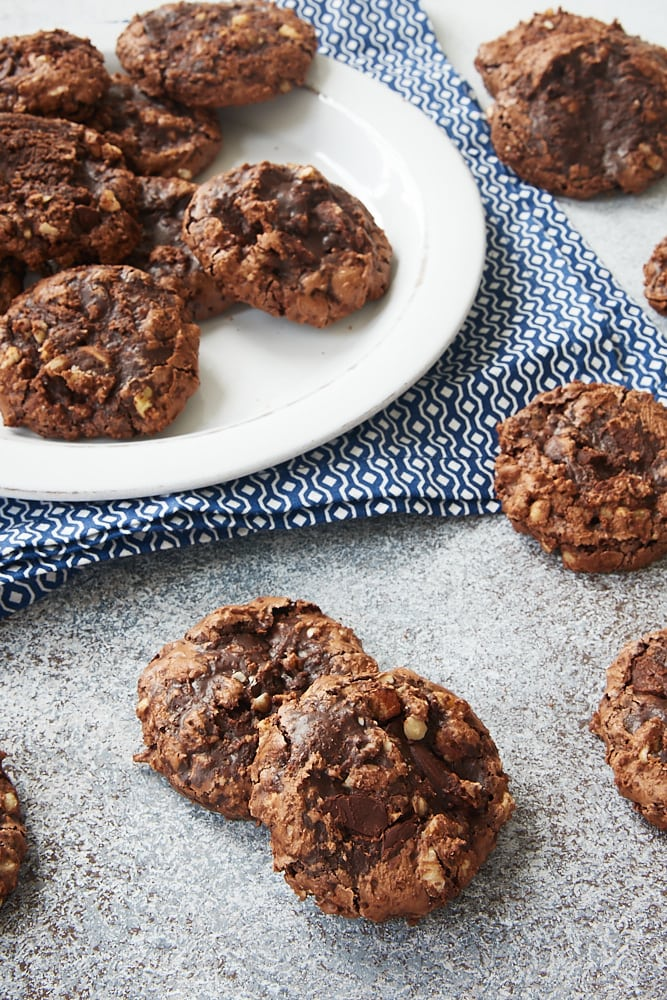 several Flourless Chocolate Hazelnut Cookies scattered on a gray surface