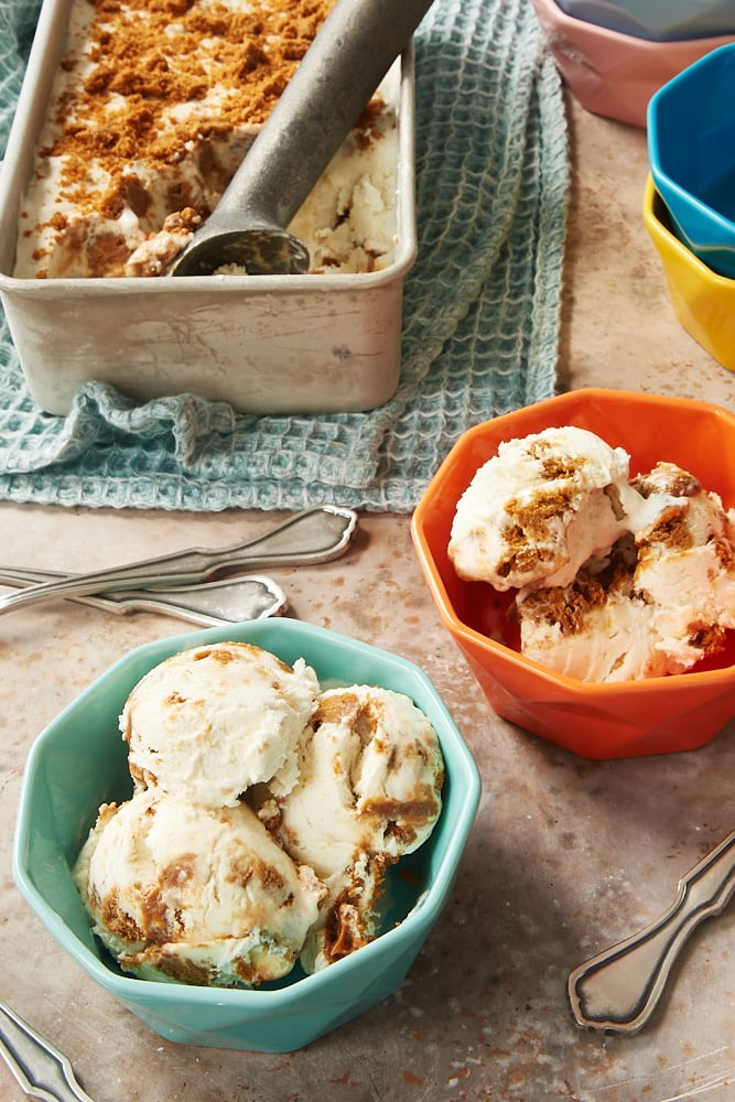 bowls of No-Churn Dulce de Leche Biscoff Ice Cream with a metal pan of remaining ice cream in the background