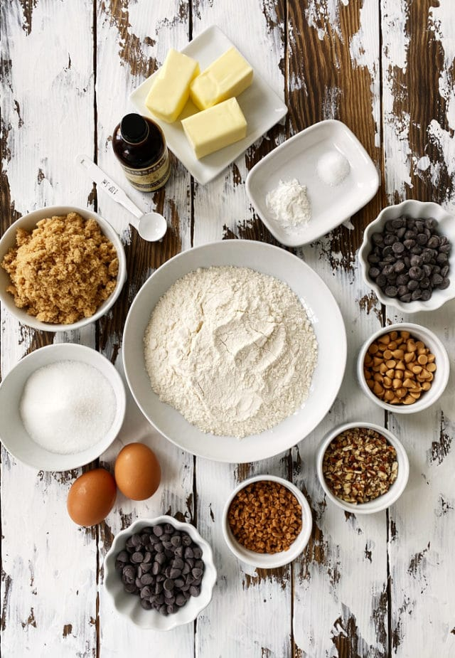 ingredients for chocolate chip cookie bars, including flour, butter, brown sugar, and various add-ins