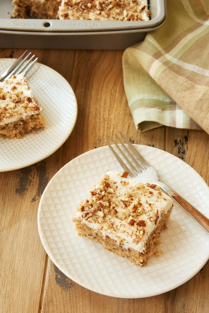 Frosted Zucchini Bars served on white and beige plates