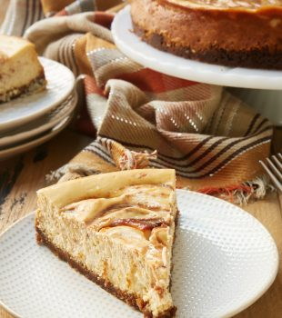 slice of Apple Butter Cheesecake on a white and beige plate