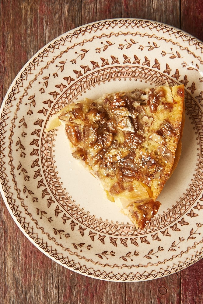 slice of Apple Bourbon Clafoutis on a brown-rimmed floral plate