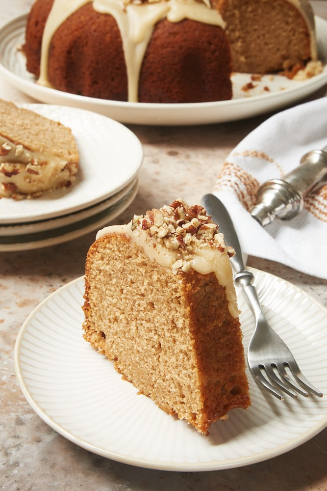 Brown Sugar Spice Cake with Caramel Rum Glaze served on white and beige plates