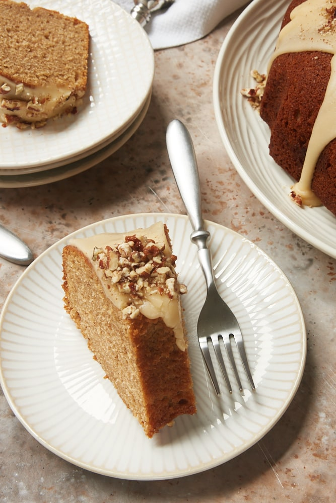 slices of Brown Sugar Spice Cake with Caramel Rum Glaze on white and beige plates