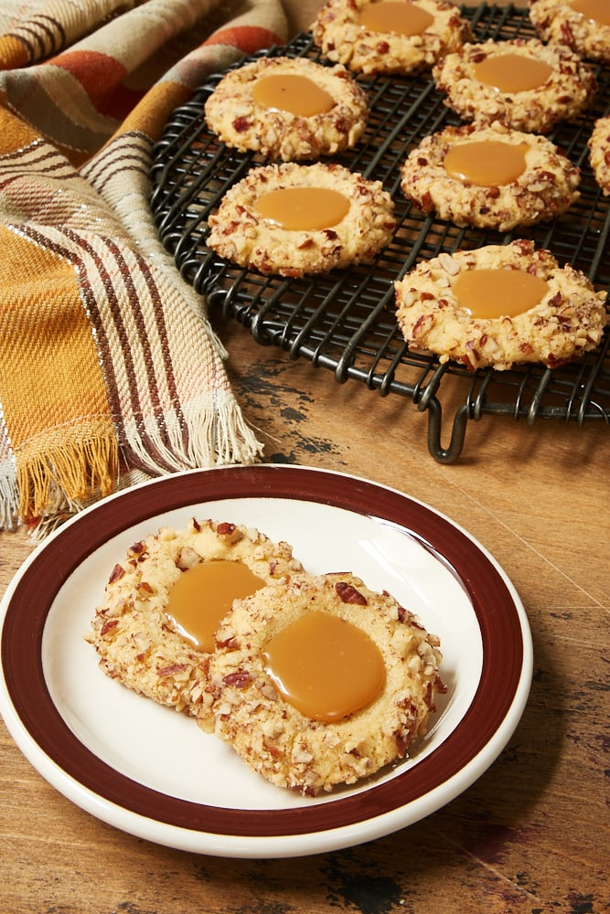 Caramel Pecan Thumbprint Cookies on a brown-rimmed white plate