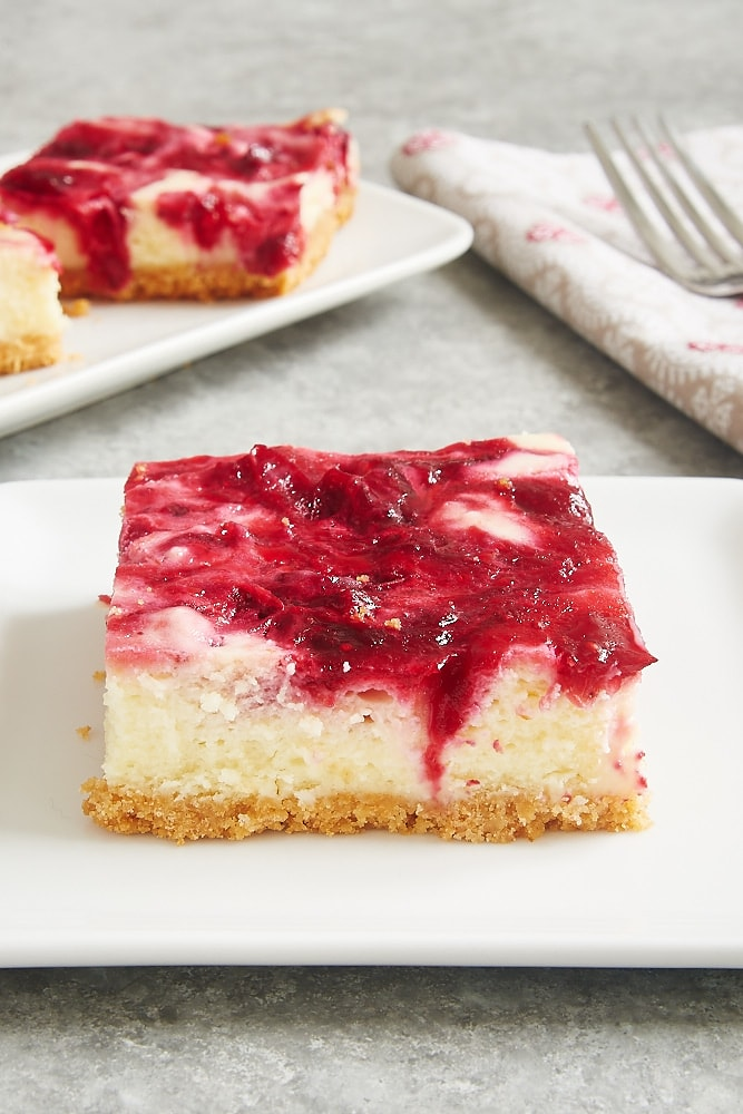 Cranberry White Chocolate Cheesecake Bars served on square white plates