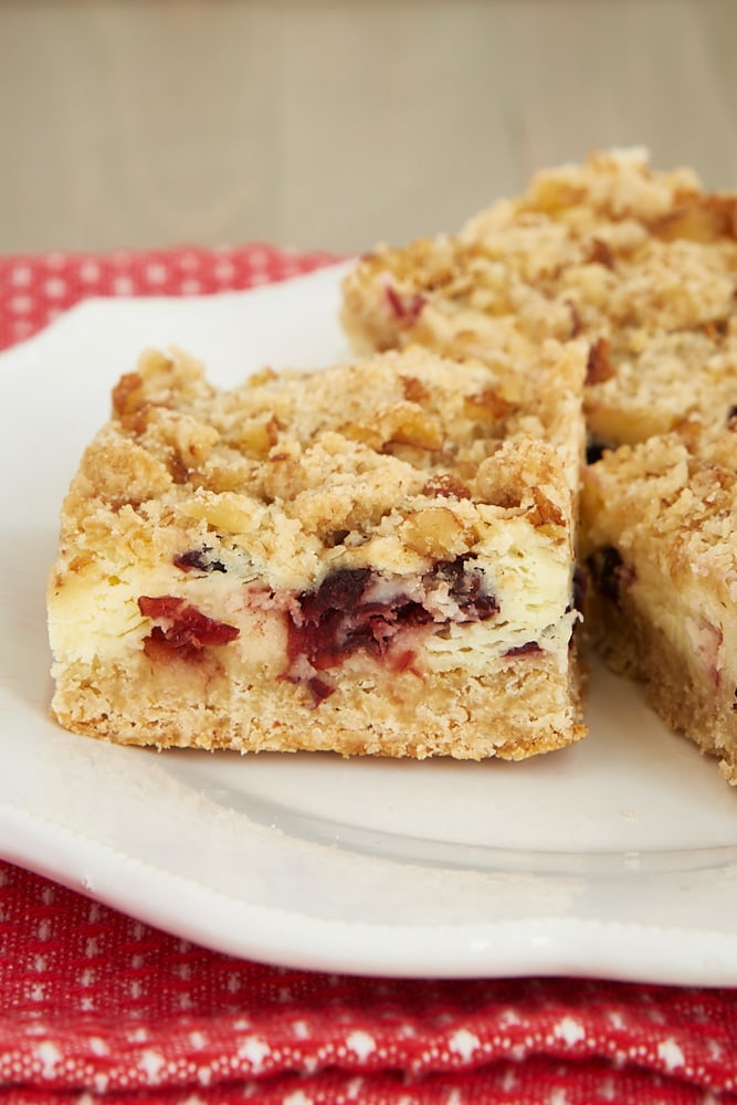 Cranberry Crumble Cheesecake Bars on a white plate