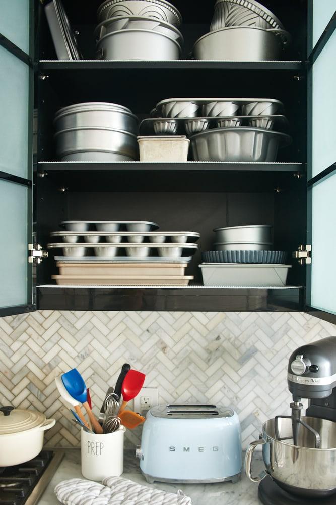 baking pans organized in a kitchen cabinet