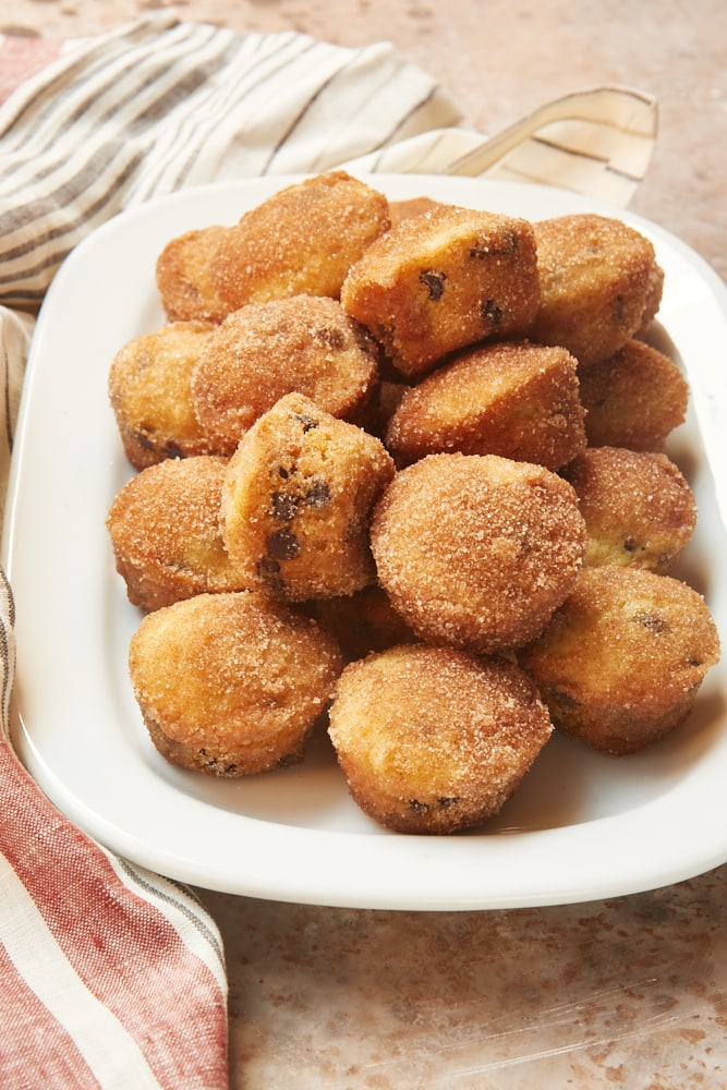 Mini Chocolate Chip Doughnut Muffins piled on a white tray