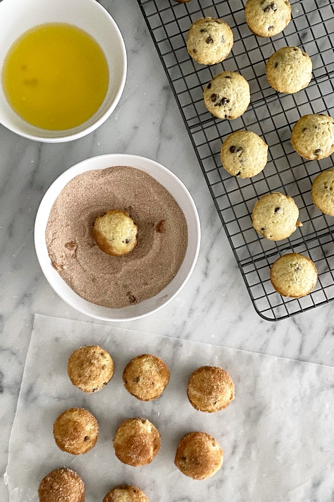 Mini Chocolate Chip Doughnut Muffins being dipped into butter and cinnamon-sugar