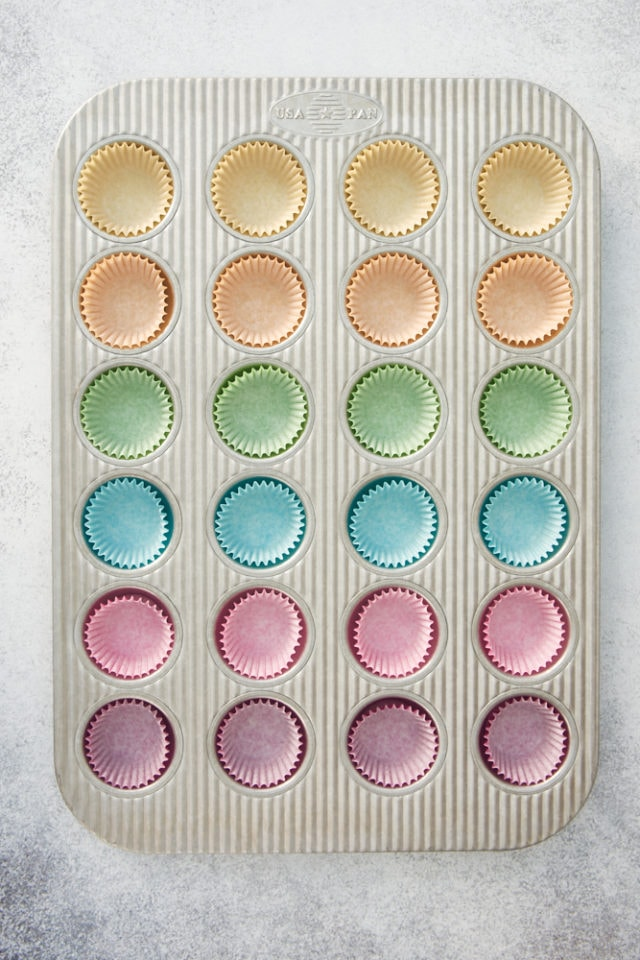 overhead view of different color cupcake liners in a mini muffin pan