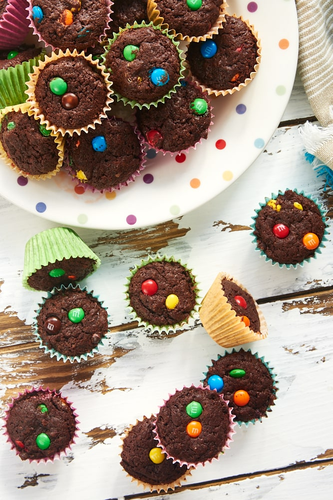 M&M Brownie Bites on a multi-colored polka dot plate and on a white wooden surface