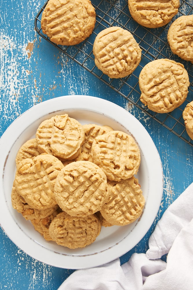 overhead view of Peanut Butter Cookies on a white plate and on a wire cooling rack