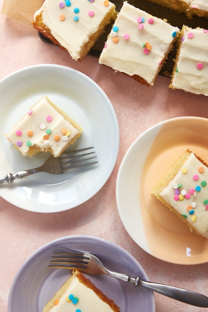overhead view of slices of Vanilla Cake with Vanilla Frosting on colorful plates