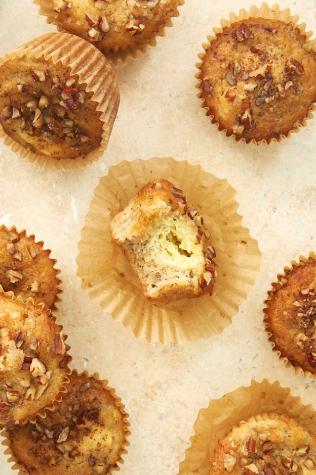 overhead view of Banana Cream Cheese Muffins on a beige surface