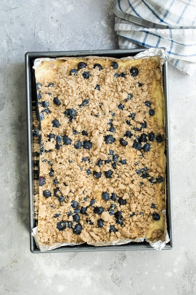 overhead view of Blueberry Crumb Cake batter topped with blueberries and crumb topping