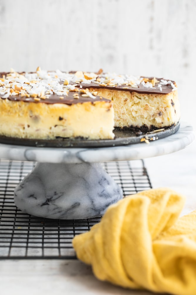 Chocolate Coconut Almond Cheesecake on a marble cake stand