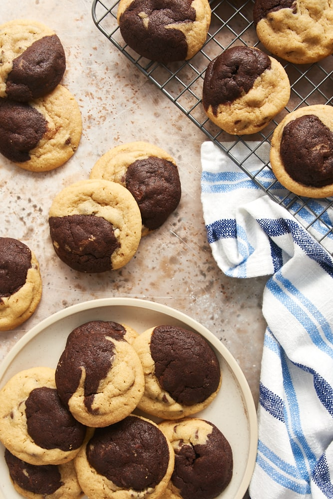 Chocolate Peanut Butter Swirl Cookies on a wire rack, a beige plate, and a light brown surface