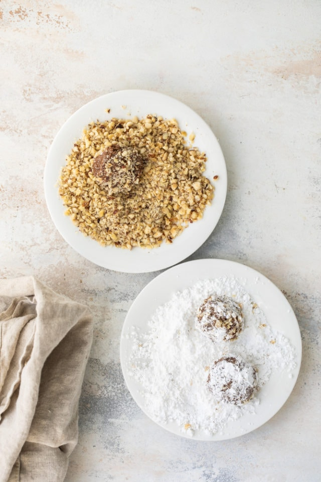 Hazelnut Crinkle Cookies dough being rolled in chopped hazelnuts and confectioners' sugar