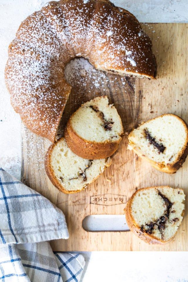 overhead view of Sour Cream Hazelnut Bundt Cake on a wooden cutting board