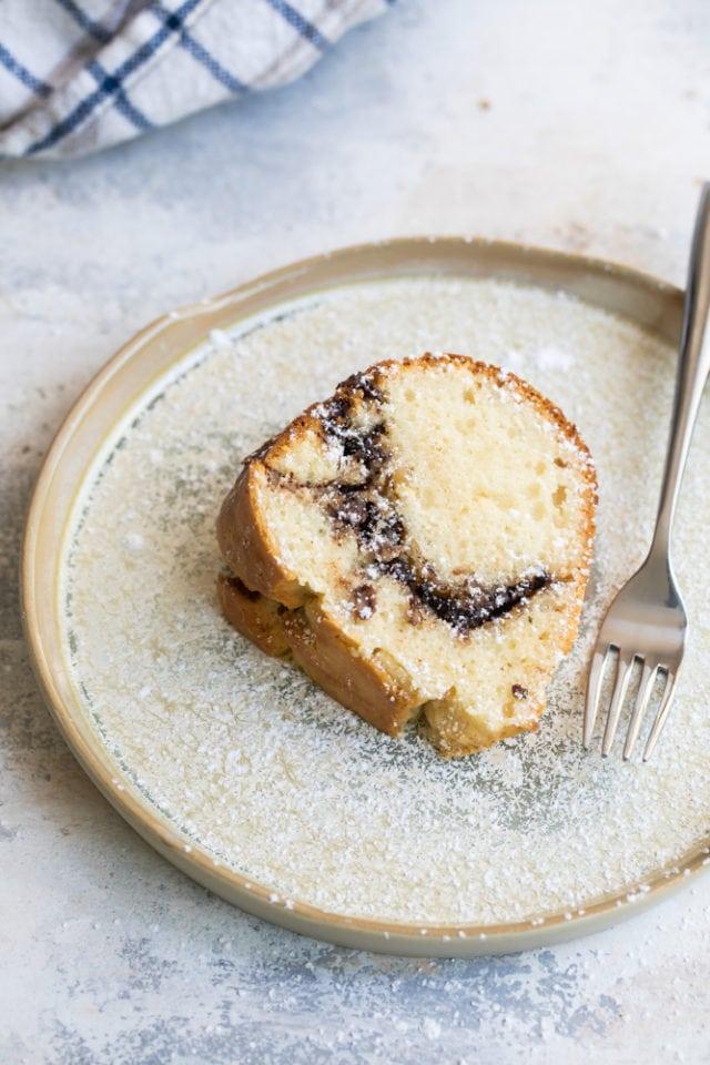 slice of Sour Cream Hazelnut Bundt Cake on a beige plate
