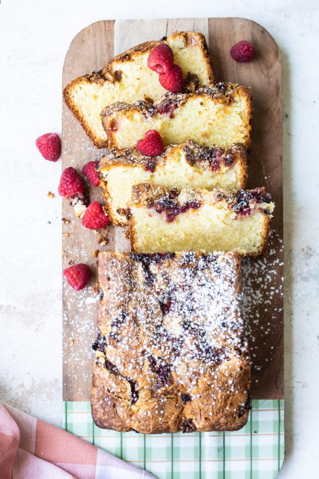 overhead view of Raspberry White Chocolate Almond Loaf on a wooden cutting board