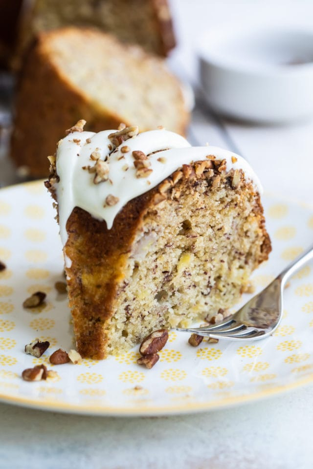 slice of Hummingbird Bundt Cake on a white and yellow plate