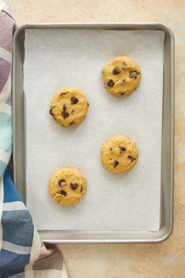 overhead view of chocolate chip cookie dough on a parchment-lined baking sheet