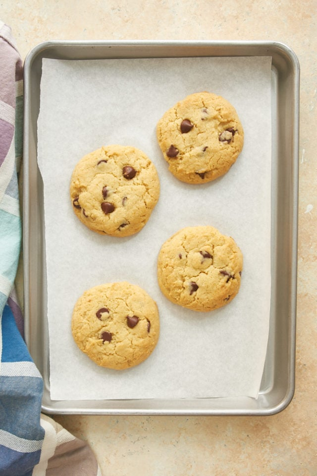 overhead view of freshly baked chocolate chip cookies on a parchment-lined baking sheet