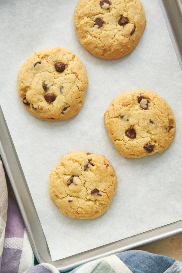 overhead view of chocolate chip cookies on a parchment-lined baking sheet