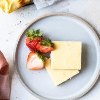 overhead view of Vanilla Bean Cheesecake Bars served with fresh strawberries