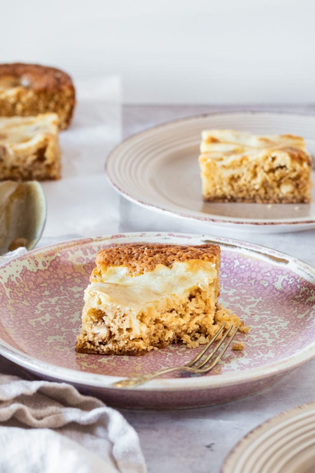 Butterscotch Cream Cheese Swirl Bars served on beige and pink plates
