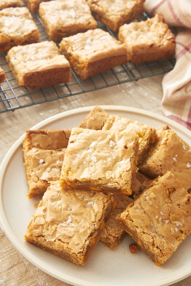 Salted Butterscotch Blondies piled on a beige plate
