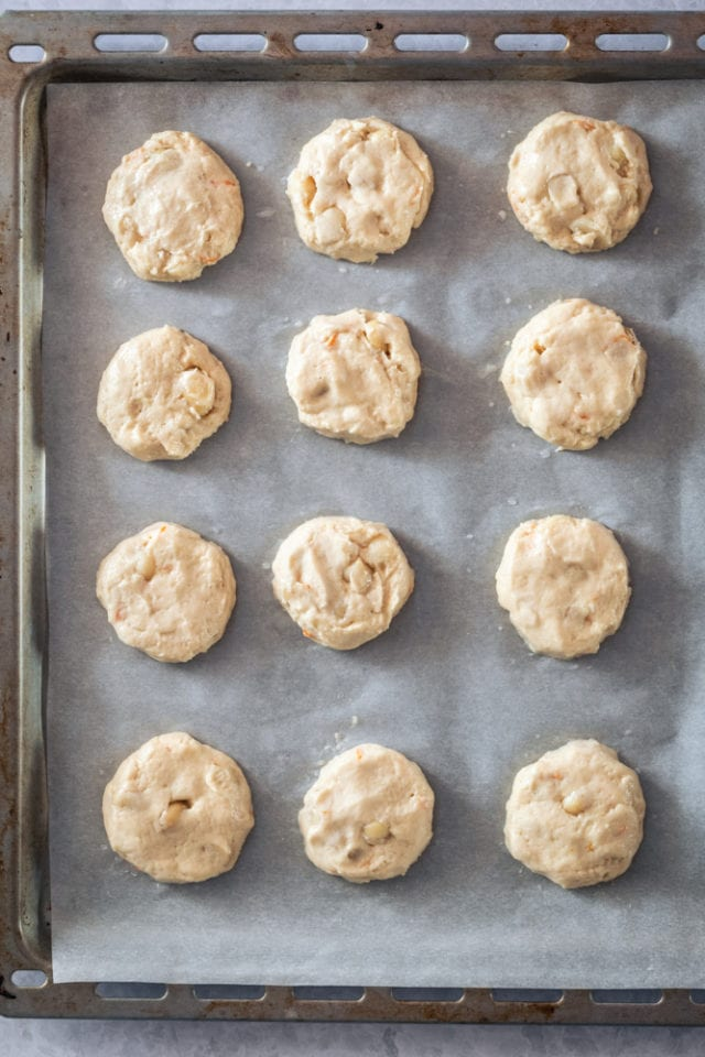 overhead view of Cream Cheese Macadamia Cookie dough on a parchment-lined baking sheet