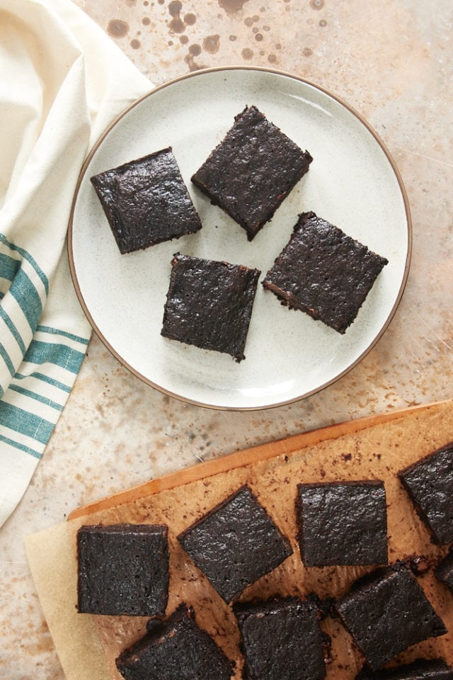 overhead view of Double Chocolate Zucchini Brownies on a beige plate and a wooden cutting board