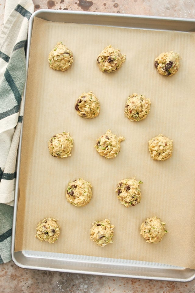 overhead view of Zucchini Oatmeal Chocolate Chip Cookie dough portioned onto a parchment-lined baking sheet