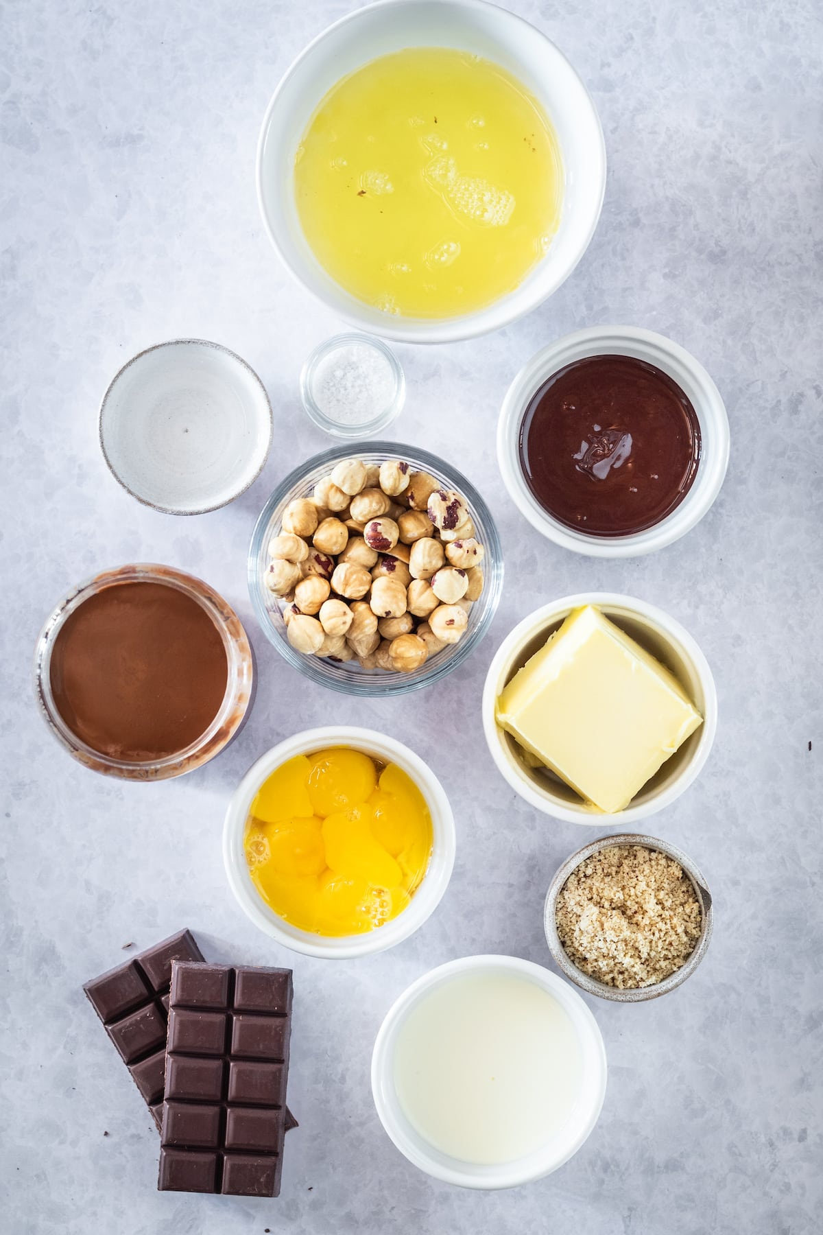 ingredients for chocolate cake with hazelnuts in small bowls