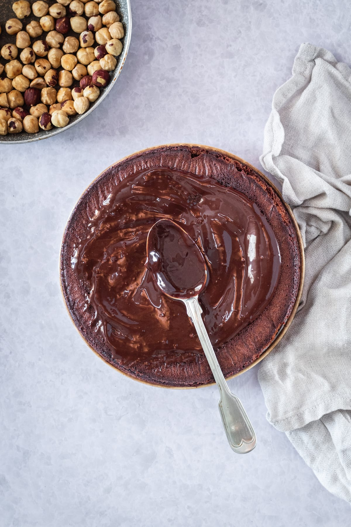 frosting a chocoalte cake with a spoon