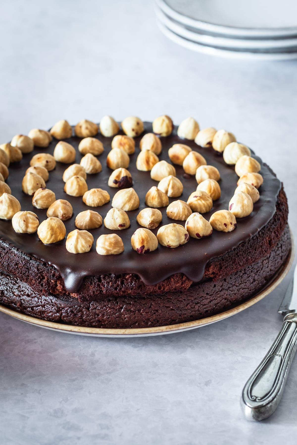 whole chocolate cake topped with toasted hazelnuts