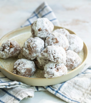 plate of powdered sugar-dusted coco macadamia nut cookies