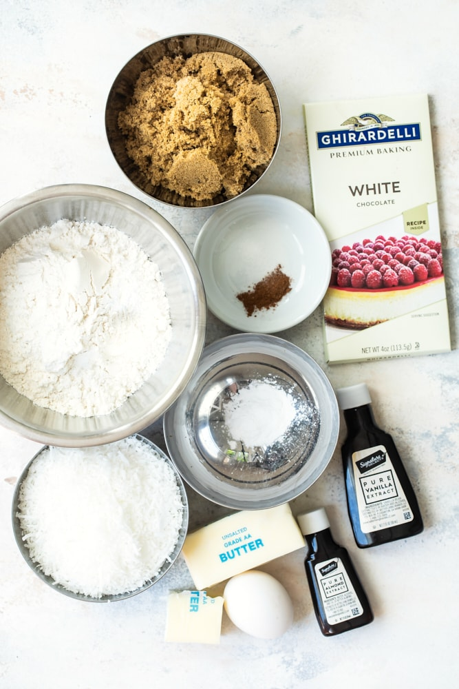 ingredients for white chocoaltee coconut cookies with flour, sugar, vanilla and almond extract
