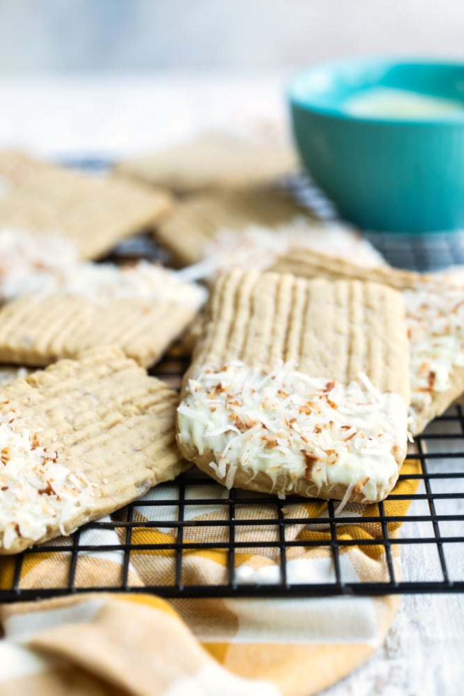 toasted coconut and white chocolate shortbread cookies on a wire rack